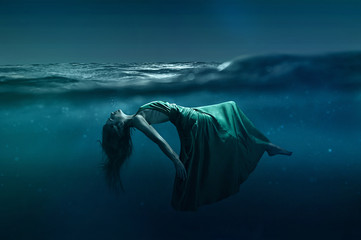 Woman floating underwater Wall mural
