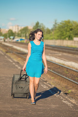 The girl with a suitcase goes along a railway way