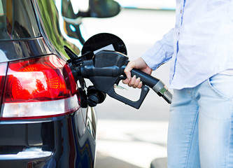 Closeup woman at gas station, filling up her car tank