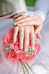 hand the bride and groom with the rings lying on bouquet