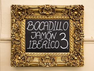 Blackboard announcing jamon iberico sandwiches in Spain.