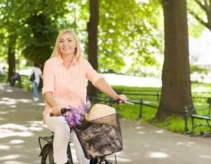 Happy beautiful woman riding a bike at park