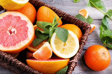 Fresh citrus fruits with green leaves in wicker basket