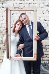 Vertical photo of newlywed couple looking through portrait frame