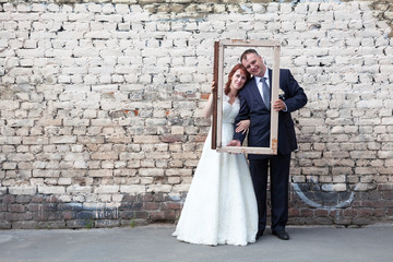 Newlywed couple holding portrait frame, brick wall