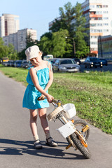 Young girl holding her bicycle