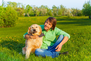 Smiling father with dog sitting on ground in park