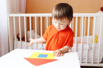 baby constructing paper house