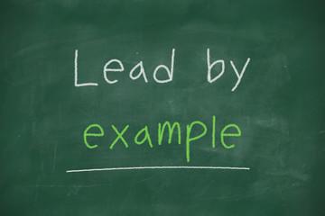 Lead by example handwritten on blackboard
