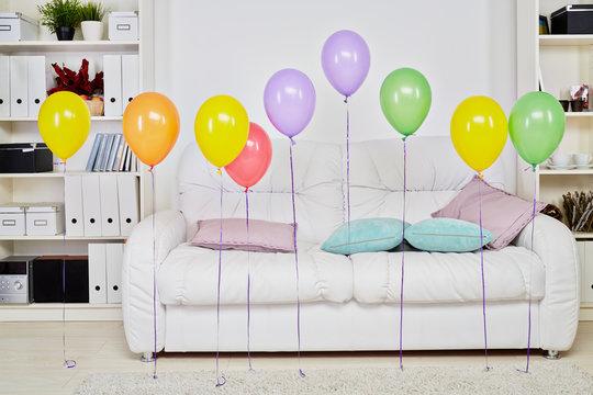 Interior of room with big soft white sofa, light carpet