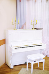 Simple white piano with yellow candles near window