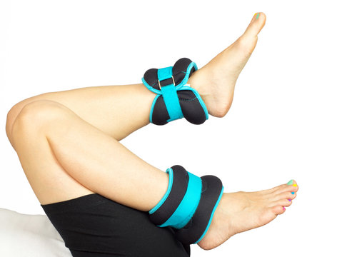 Woman's feet exercising with ankle weights, isolated