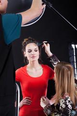 Applying powder on model's face