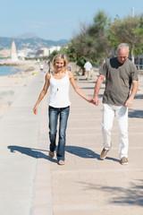 glückliches älteres paar geht am ufer entlang