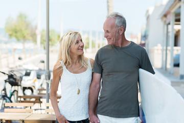 entspanntes älteres paar mit surfbrett