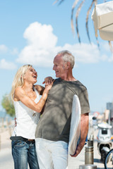 glückliches älteres paar mit surfbrett im urlaub