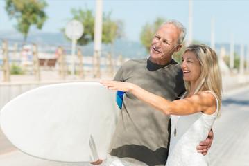 glückliches best-ager paar mit surfbrett