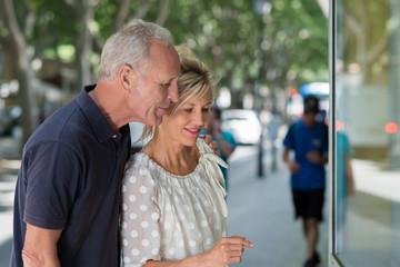 glückliches älteres paar schaut in schaufenster