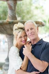 romantisches älteres paar umarmt sich am brunnen