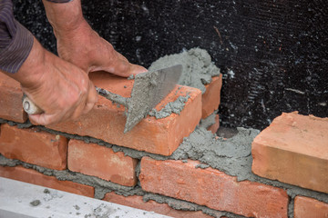 Builder worker with trowel building brick wall