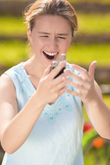 Angry and Furious Young Caucasian Woman With Cellphone on Hands
