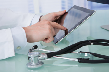Doctor Using Digital Tablet At Desk