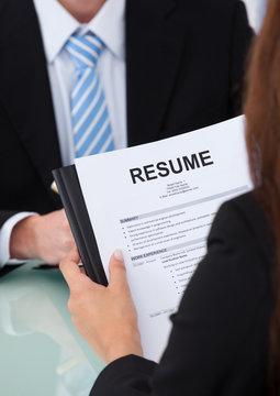 Female Candidate Holding Resume At Desk