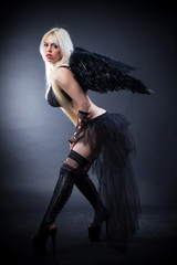 Blond female angel with black wings on a black background