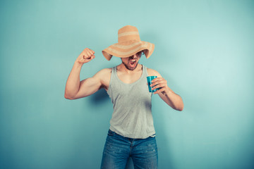 Happy young man drinking from blue cup