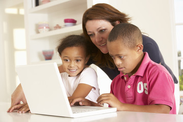 Mother and Downs Syndrome son with laptop