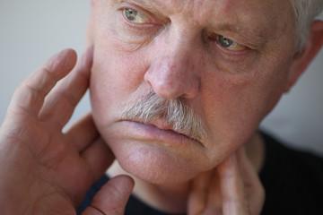 senior man touches his sore jaw area