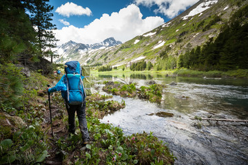 Hiker is walking by mountain lake in Altai mountains, Russia