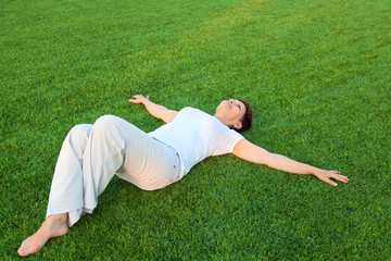 attractive middle-aged woman in a white shirt lying on the lawn
