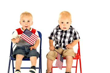 two cute blond boys holding American flags sitting
