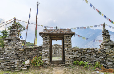 Buddhist stone made gate with prayer flags