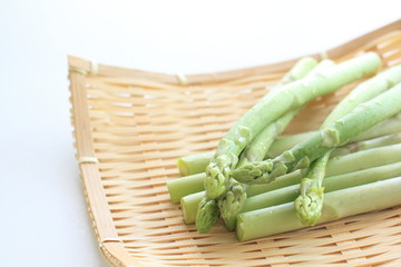 green asparagus on bamboo basket