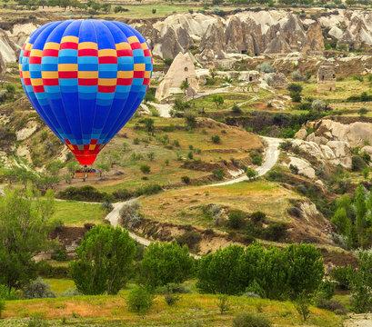 Hot air balloon flying mountain valley Göreme National Park and the Rock Sites of Cappadocia Turkey