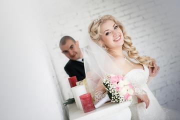 beautiful bride an groom on their wedding day near fireplace