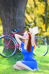 Redhead girl in blue dress with red bicycle in the park.