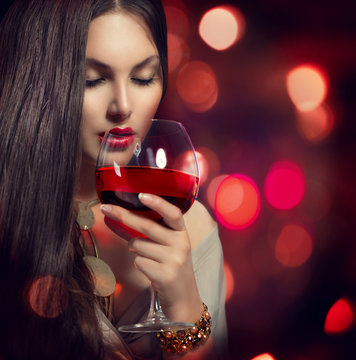 Beauty Young sexy woman drinking red wine over night background