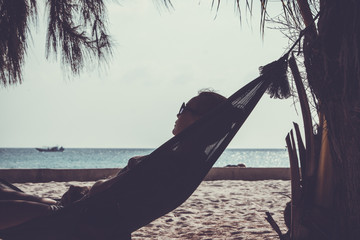 woman in sunglasses lying at hammock by the beach. Koh Phangan