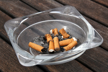 ashtray and cigarettes on wooden background