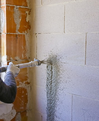 Worker performs internal plaster with machine applying plaster