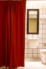 Small bathroom red curtain . View of washbasin cabinet with mirr