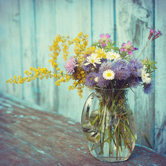 bouquet of garden flowers and healing herbs in glass jug on old