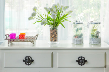 Vase with flower and vintage decorate on table with windowsill