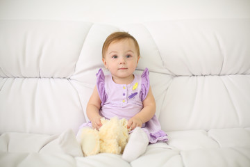 Little baby in dress with toy sits on white sofa at home
