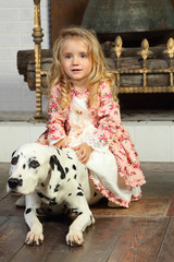 Happy pretty little girl in medieval costume sits with dalmatian