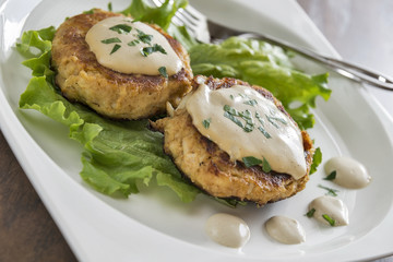 Crab cakes with a creamy mustard sauce and fresh parsley
