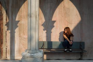 dramatic sunlight girl sitting on wooden bench